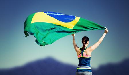 raise the white flag: Rear view of sportswoman raising a brazilian flag against dark blue green background