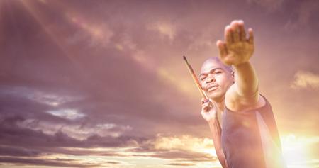 lanzamiento de jabalina: Retrato de deportista practicando un lanzamiento de jabalina contra el cielo nublado