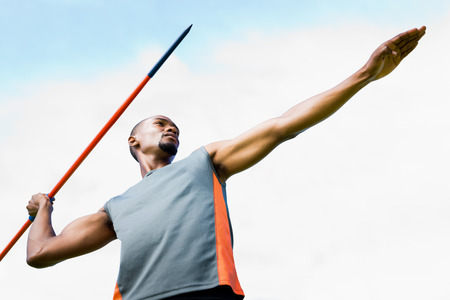 lanzamiento de jabalina: Low angle view of sportsman practising javelin throw  against blue sky with clouds Foto de archivo