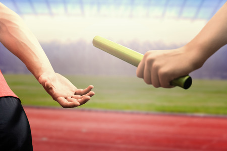 Athlete passing a baton to the partner against race track