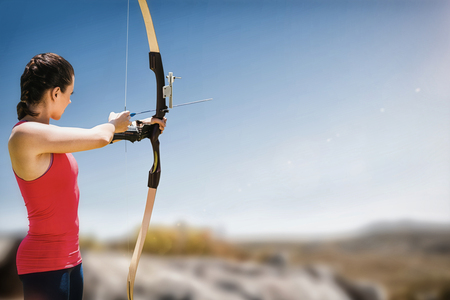 Side view of woman practicing archery against mountain trail