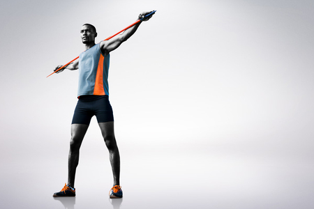athleticism: Low angle view of athletic man holding his javelin against grey background
