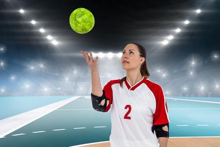 terrain de handball: Sportswoman posant avec balle contre terrain int�rieur de handball