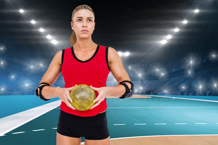 elbow pad: Female athlete with elbow pad holding handball against handball field indoor