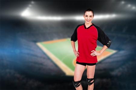 terrain de handball: Athlète féminine posant avec coudière et genouillère contre terrain intérieur de handball