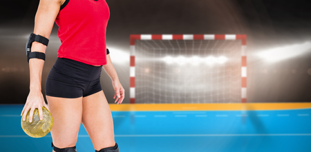 elbow pad: Female athlete with elbow pad holding handball against digital image of handball goal