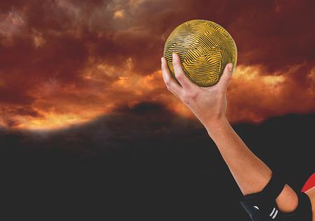 elbow pad: Female athlete with elbow pad holding handball against gloomy sky Stock Photo