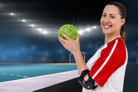 terrain de handball: Sportswoman posant avec balle contre terrain intérieur de handball