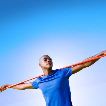 lanzamiento de jabalina: Deportista con los ojos cerrados que se prepara para el lanzamiento de jabalina contra el cielo azul