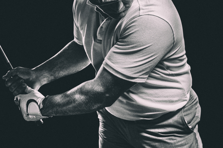 Portrait of golf player taking a shot against black background