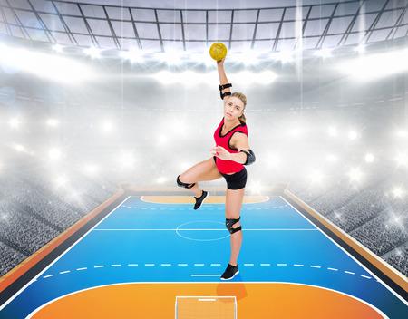 athleticism: Female athlete throwing handball against handball field indoor