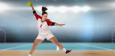 terrain de handball: Sportswoman lancer une balle contre l'image num�rique de terrain int�rieur de handball Banque d'images