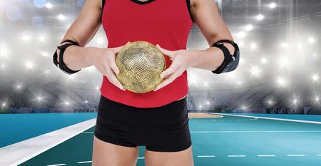 athleticism: Female athlete with elbow pad holding handball against handball field indoor