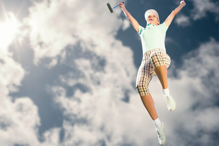 Woman jumping with golf club against bright blue sky with clouds