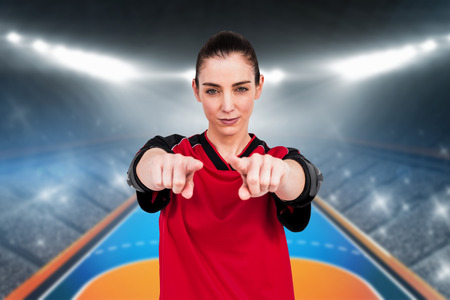 terrain de handball: Female athlete posing with elbow pad and pointing the camera against handball field indoor