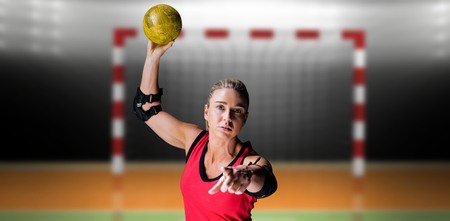 elbow pad: Female athlete with elbow pad throwing handball against digital image of handball goal