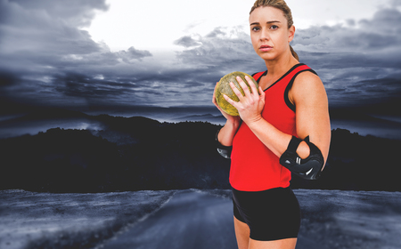 elbow pad: Female athlete with elbow pad holding handball against road leading out to the horizon at night Stock Photo