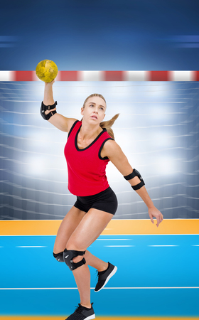 elbow pad: Female athlete with elbow pad throwing handball against handball field indoor