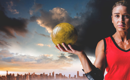 elbow pad: Female athlete with elbow pad holding handball against city on the horizon