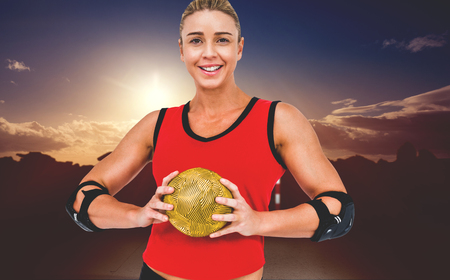 elbow pad: Female athlete with elbow pad holding handball against composite image of landscape Stock Photo