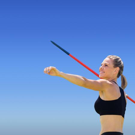 lanzamiento de jabalina: Retrato de deportista feliz está practicando el lanzamiento de jabalina contra el cielo azul brillante