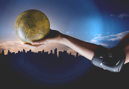 elbow pad: Female athlete with elbow pad holding handball against picture of a city by sunrise Stock Photo