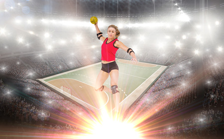 terrain de handball: Female athlete with elbow pad throwing handball against handball field indoor