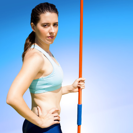 javelin: Portrait of serious sportswoman holding a javelin  against blue sky