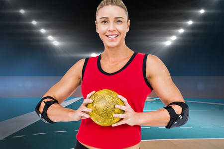 female elbow: Female athlete with elbow pad holding handball against handball field indoor