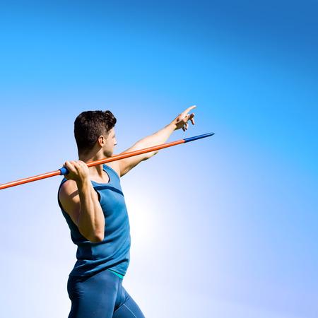 lanzamiento de jabalina: Vista trasera del deportista practicando tiro de jabalina contra el cielo azul