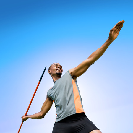 lanzamiento de jabalina: Low angle view of sportsman practising javelin throw  against blue sky Foto de archivo