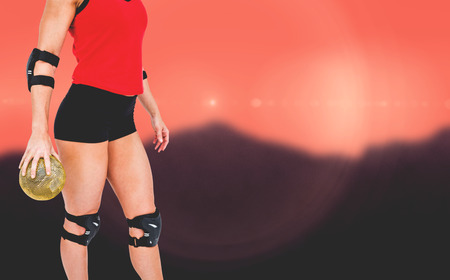 elbow pad: Female athlete with elbow pad holding handball against blurred mountains Stock Photo