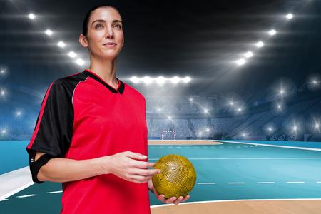 Athlète féminine tenant un ballon de la main sur le terrain à l'intérieur de handball