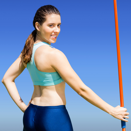 legging: Rear view of sporty woman holding a javelin against bright blue sky Stock Photo