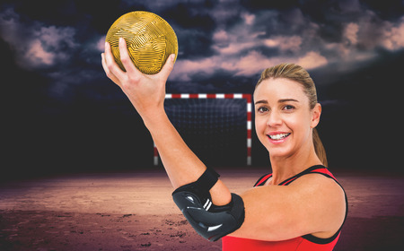 elbow pad: Female athlete with elbow pad holding handball against dark cloudy sky Stock Photo
