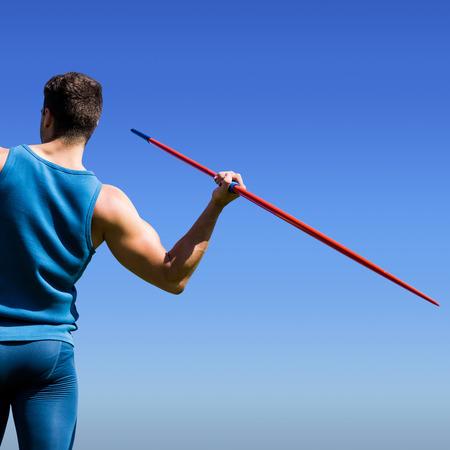 lanzamiento de jabalina: Vista trasera del deportista practicando tiro de jabalina contra el cielo azul brillante Foto de archivo