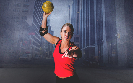 elbow pad: Female athlete with elbow pad throwing handball against urban projection on wall Stock Photo
