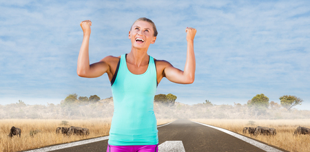 arms up: Athletic woman with arms up against savannah road landscape Stock Photo
