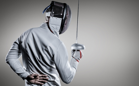 Man wearing fencing suit practicing with sword against grey vignette Imagens - 58401423