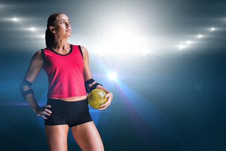 female elbow: Female athlete with elbow pad holding handball against spotlights Stock Photo
