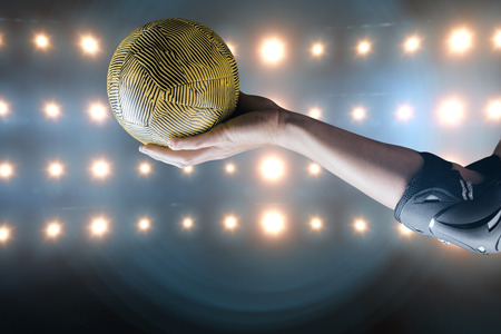 elbow pad: Female athlete with elbow pad holding handball against composite image of orange spotlight Stock Photo