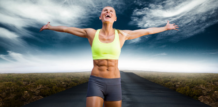stretched: Fit woman celebrating victory with arms stretched against view of an empty street