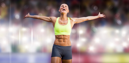 winning pitch: Fit woman celebrating victory with arms stretched against sports arena