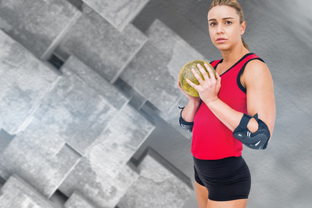 elbow pad: Female athlete with elbow pad holding handball against grey tile design Stock Photo