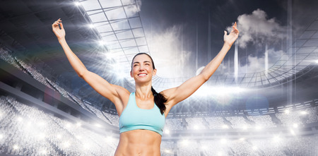 winning pitch: Portrait of happy sportswoman is raising arms  against sports arena