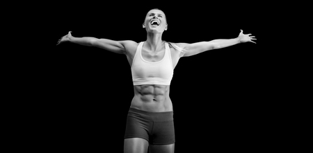 stretched: Fit woman celebrating victory with arms stretched against black background Stock Photo