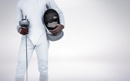 swordsman: Swordsman holding fencing mask and sword against grey vignette