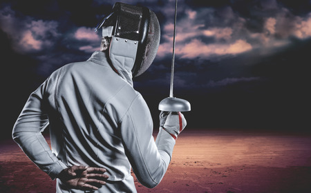 Man wearing fencing suit practicing with sword against dark cloudy sky Imagens