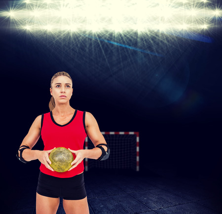 elbow pad: Female athlete with elbow pad holding handball against view of spotlights