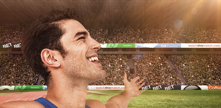 winning pitch: Excited male athlete with arms outstretched against view of a stadium